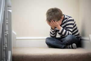 A boy cries on the staircase.