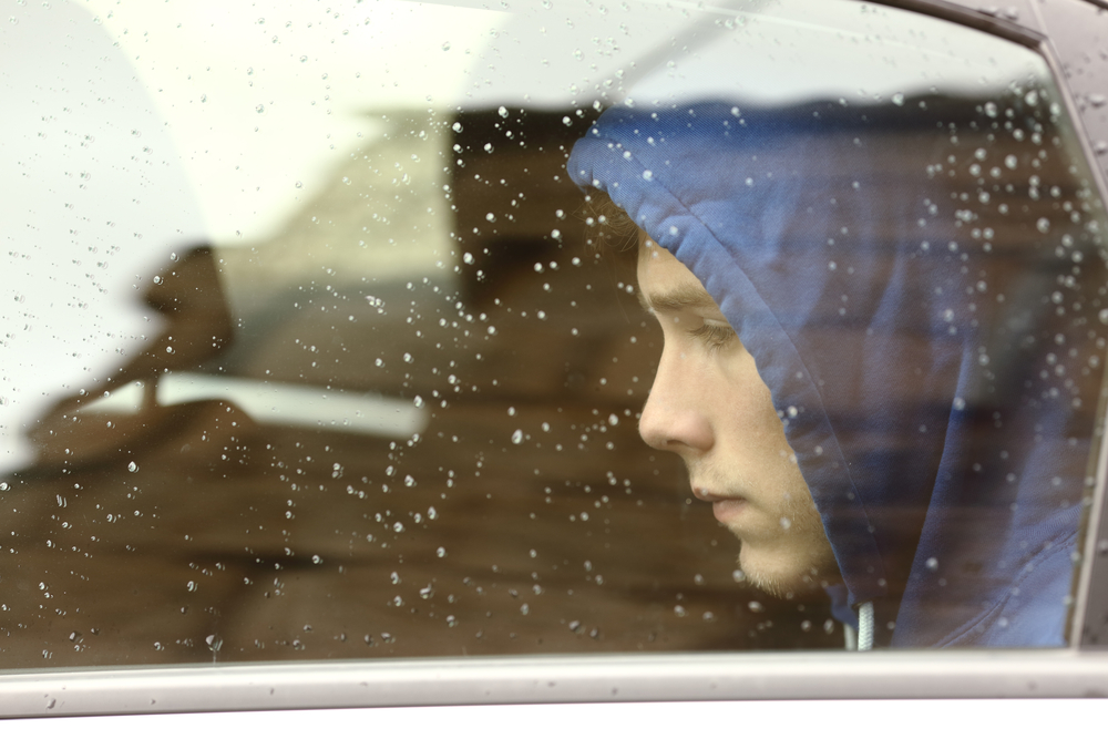 Sad teenager through rainy window