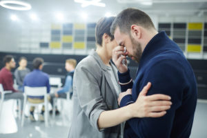 Woman comforting grieving man